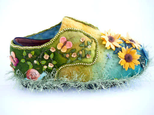 one side of sunflower shoe showing detatil of vine with flowers,butterfly and snail, the other side has the vine and a spider web